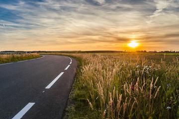 Asphalt road in the flat landscape of the Netherlands during summer evening