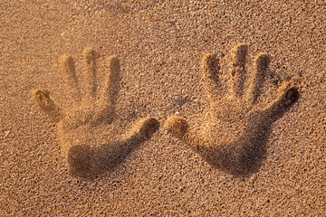 Two hand prints on the sand and sun