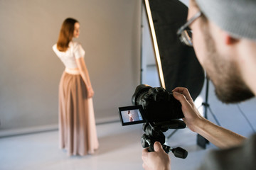POV of photographer during studio session. Screen of professional camera with portrait of model on it. Fashion photoshoot backstage