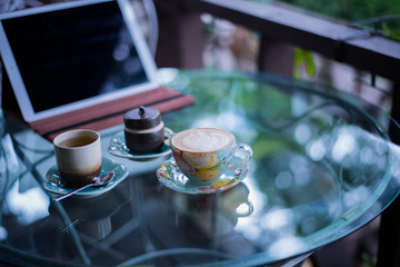 Cup of hot drink with coffee on table.