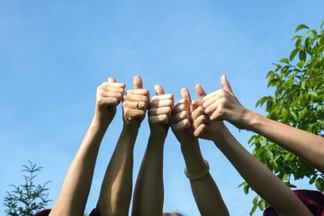 Thumbs up, friends raise their hands and show their thumbs as a positive gesture on a sunny day against the blue sky
