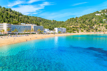 Fototapete - Azure sea water and hotel buildings on beach in Cala San Vicente bay, Ibiza island, Spain
