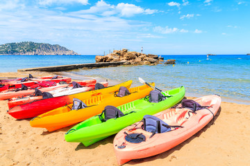 Fototapete - Colourful kayaks on sandy Es Figueral beach, Ibiza island, Spain