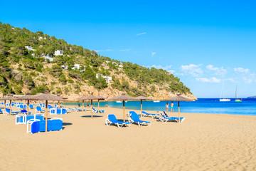 Sandy beach with umbrellas and sunbeds in Cala San Vicente bay on sunny summer day, Ibiza island, Spain
