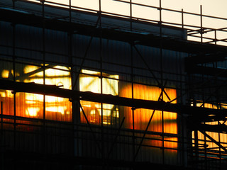 color detail photography of scaffolding around industrial building in sunset