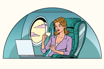 Businesswoman in business class of the aircraft works at a lapto