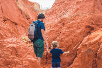 Father and son travelers in red canyon near Mui Ne, southern Vietnam. Traveling with children concept