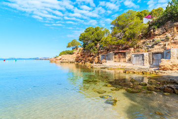 View of beautiful Cala Gracio beach with boat houses on shore at early morning, Ibiza island, Spain