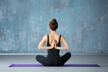 Young woman practicing yoga near grey wall indoors