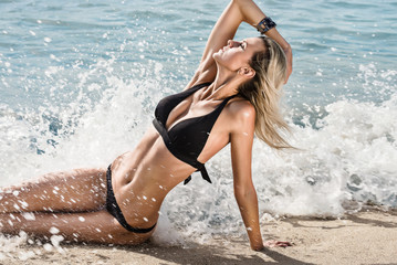Fashion model sits on the sand and poses in the waves and water spray. Beach scene