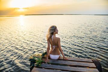 woman in bikini sits on the pier