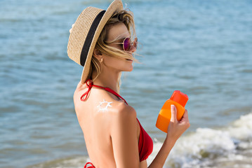 Young woman is using sunblock cream on the beach near the sea
