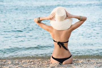 Slim blonde woman in a straw hat near the sea back view