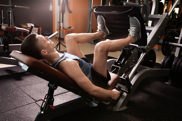 Sporty young man training legs in gym