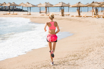 Attractive young athletic woman is running along the beach