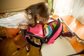 Image from high point of cute schoolgirl looking inside of her backpack
