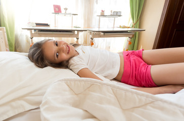 Cute smiling girl lying in bed at sunny morning