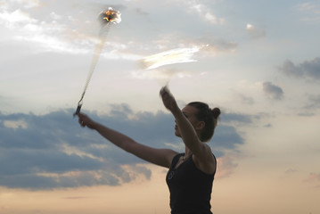 Attractive Woman Fire Performer -  sunset fire dancing  at the beach