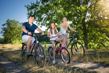 Young parents riding on bicycles with their daughter at park