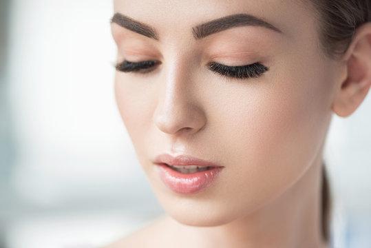 Thoughtful beautiful girl using visage cosmetics