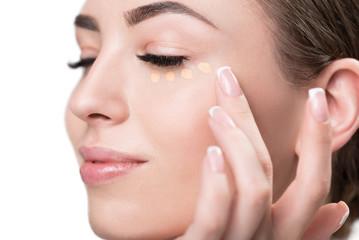 Happy beautiful girl applying facial cosmetic
