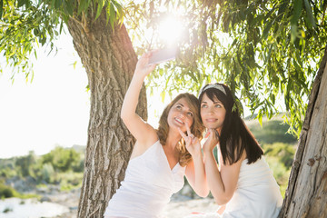 Best friend girls sitting on a tree on the sunny beach and taking selfie on camera