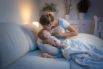 Young mother feeding her baby from bottle in bed at night