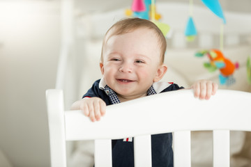 Smiling 9 month old baby standing in white wooden crib