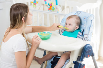 Young woman feeding her baby from spoon with apple sauce