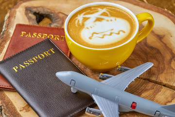Passports, coffee and toy airplane. Latte cup on wood board. Air travel tips.