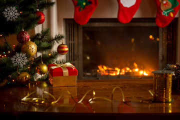 Christmas background with burning fireplace, Christmas tree, gift box and table