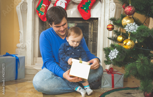 young father and cute baby son opening christmas gifts on floor
