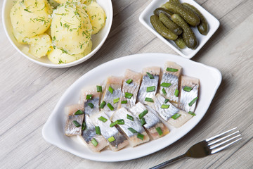 Pieces of herring with onions, gherkins and boiled potatoes. Selective focus