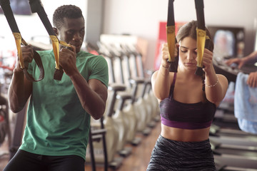 black man and white young woman doing trx exercices