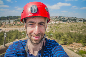 Extreme professional climber taking selfie photo on the top of climbing tower