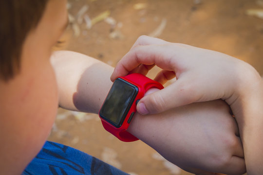 Cute young boy looking at his red smart watch and touching it