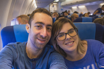 Happy couple taking selfie with smartphone or camera inside airplane