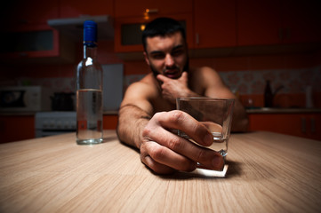 Young caucasian man drinking alcohol at home