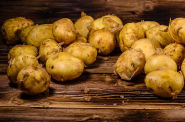 Pile of the young potato on wooden table