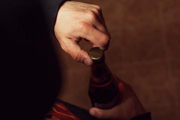 Closeup of male hands opening beer bottle.