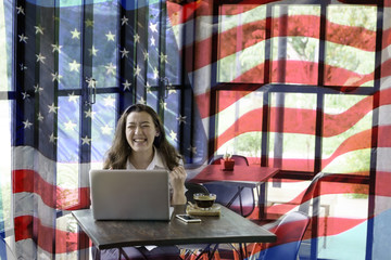 Patriotic composite of happy young half Thai-American woman in happy moment over background of  American flag blowing in the wind.4th July