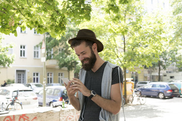 Young hipster guy with beard and hat smiling and laughing reading text messages on his smartphone. Outdoors