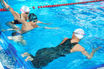The swimming coach shows exercises for children