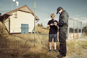 Police man asking teenager in terrain