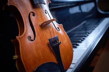 деревянная скрипка на черном рояле
