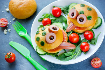 Cute frog shaped hamburger on a plate with fresh vegetables