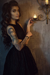 Portrait of chic young tattooed woman with luxurious long wavy silky hair and perfect make up wearing black lace dress with naked sides standing in the dark shabby room at the burning candles