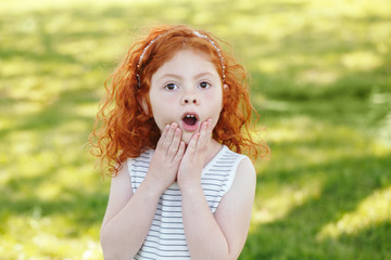 Portrait of cute adorable surprised  little red-haired Caucasian girl child in striped dress in park outside, playing  crying screaming in fear, happy lifestyle childhood concept