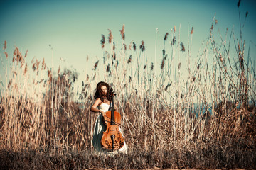 Girl with a cello in a tall grass