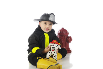 "Happy Little ""fireman"" with his toy fire dog. On a white background."